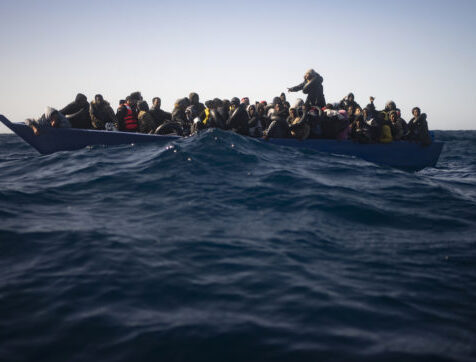 Migrants from Eritrea, Egypt, Syria and Sudan, wait to be assisted by aid workers of the Spanish NGO Open Arms, after fleeing Libya on board a precarious wooden boat in the Mediterranean sea, about 110 miles north of Libya, on Saturday, Jan. 2, 2021. (AP Photo/Joan Mateu)